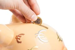 Räcka att sätta in ett mynt in i en spargris, begreppet för affär och spara pengar Royaltyfri Foto