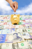 Räcka att sätta ett mynt in i en spargris med olik valuta Royaltyfri Bild