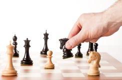 Räcka att sätta ett svart schackstycke på en tabell Arkivfoto