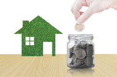 Räcka att sätta myntet in i den glass behållaren av att köpa ett nytt hus - sparande pengar för det framtida begreppet Royaltyfria Foton