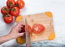 Räcka att skiva den nya trädgårds- tomaten på naturlig bambuskärbräda Arkivbilder