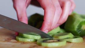 Räcka att skiva en kiwi med en kniv på träbrädet, slut upp, 4k lager videofilmer