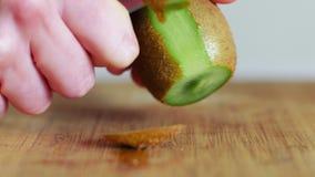Räcka att skiva en kiwi med en kniv på träbrädet, slut upp, 4k arkivfilmer