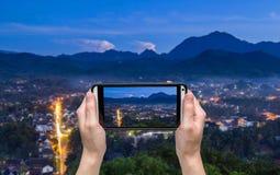 Räcka att ta fotoet på synvinkeln och landskap i luangprabang Arkivfoto
