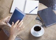 Räcka att trycka på på datorminnestavlaskärmen med svart kaffe och PA Royaltyfria Bilder