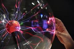Räcka att trycka på med elektriskt plasma för finger i den glass sfären arkivbilder