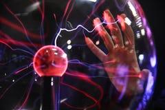 Räcka att trycka på med elektriskt plasma för finger i den glass sfären royaltyfria foton