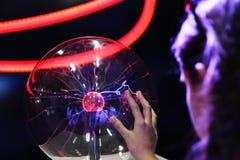 Räcka att trycka på med elektriskt plasma för finger i den glass sfären fotografering för bildbyråer