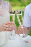 Räcka bruden och brudgummen med exponeringsglas av champagne Arkivfoto