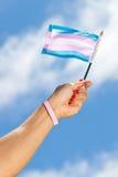 Räcka den hållande övre Transgenderstolthetflaggan in mot himlen Fotografering för Bildbyråer