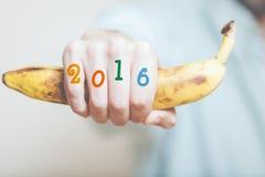 Räcka den hållande bananen På fingernummer av året Royaltyfri Bild