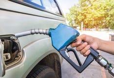 Räcka den hållande bränsledysan som tankar gaspumpen för bilen Arkivfoto
