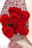 Räcka den hållande buketten av röda rosor över vit bakgrund royaltyfri foto