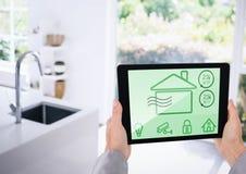 Räcka den hållande digitala minnestavlan med symboler för hem- säkerhet på skärmen Fotografering för Bildbyråer