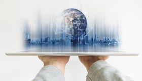 Räcka den hållande digitala minnestavlan med teknologi för anslutning för globalt nätverk och det moderna byggnadshologrammet Bes royaltyfri fotografi