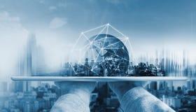 Räcka den hållande digitala minnestavlan med teknologi för anslutning för globalt nätverk och moderna byggnader Beståndsdelen av  arkivbild