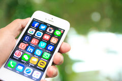 Räcka den hållande iPhonen med sociala massmediaapplikationer på skärmen Fotografering för Bildbyråer