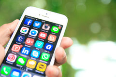 Räcka den hållande iPhonen med sociala massmediaapplikationer på skärmen Arkivfoton