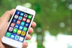 Räcka den hållande iPhonen med sociala massmediaapplikationer på skärmen Arkivbild