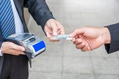 Räcka den hållande kreditkorten med affärsmannen genom att använda betalningterminalen Royaltyfria Bilder