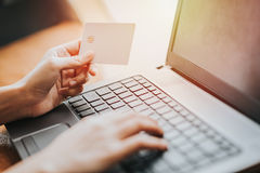 Räcka den hållande kreditkorten och användabärbara datorn för online-affär Royaltyfri Bild