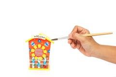 Räcka den hållande målarpenseln och målning som isoleras på vit backgroun Royaltyfria Bilder