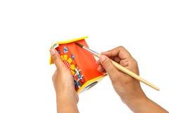 Räcka den hållande målarpenseln och målning som isoleras på vit backgroun Royaltyfri Foto