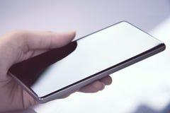 Räcka den hållande mobila smartphonen med tomt avskärmer Royaltyfri Bild