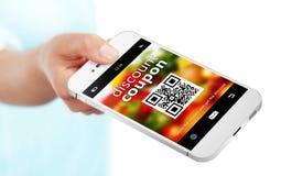 Räcka den hållande mobiltelefonen med rabattkupongen som isoleras över whi Arkivfoto