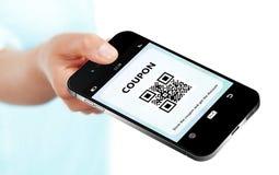 Räcka den hållande mobiltelefonen med rabattkupongen som isoleras över whi royaltyfri fotografi