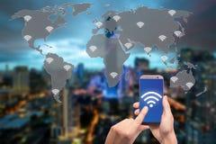 Räcka den hållande mobiltelefonen med wifisymbolen på världskarta- och stads- och nätverksanslutningsbegrepp royaltyfri fotografi