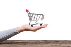 Räcka den hållande shoppingvagnen på trätabell- och vitbakgrund royaltyfri bild