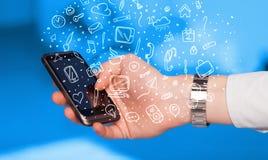 Räcka den hållande smartphonen med handen drog massmediasymboler och symboler Arkivbild
