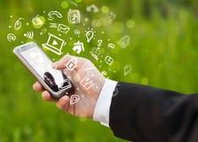 Räcka den hållande smartphonen med massmediasymboler och symbol Royaltyfri Fotografi