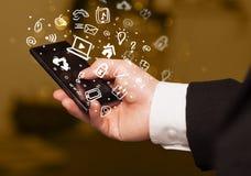 Räcka den hållande smartphonen med massmediasymboler och symbol Arkivbild