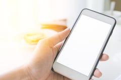 Räcka den hållande smartphonen med tomt vitt utrymme för skärmkopian Royaltyfri Fotografi