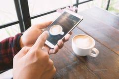 Räcka den hållande smartphonen och ta ett foto av kaffe i kaffet arkivfoton