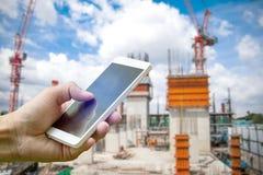 Räcka den hållande smartphonen på suddig intelligens för arbetare för konstruktionsplats fotografering för bildbyråer