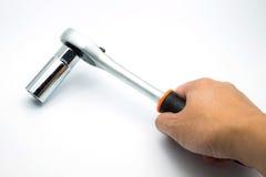 Räcka den hållande spärrhjulskiftnyckeln på den vita bakgrunden Fotografering för Bildbyråer