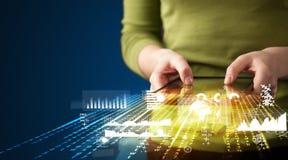 Räcka den hållande touchpadminnestavlan med grafer för affärsmarknaden Royaltyfri Foto