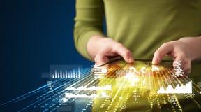 Räcka den hållande touchpadminnestavlan med grafer för affärsmarknaden Arkivfoton