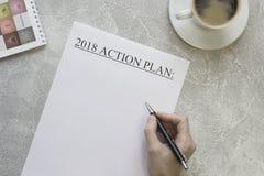 Räcka den handstil2018 handlingsplanen, en cofeekopp, en anteckningsbok Royaltyfri Fotografi