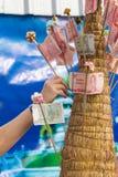 Räcka den satta thai sedeln gör in merit Arkivbild