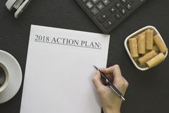 Räcka den writindhandlingsplanen 2018 och en vit bunke av kakor Royaltyfria Foton