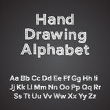 Räcka det dra alfabetet med krita verkställer Arkivfoto