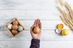 Räcka det hållande bruna ägget på vit wood bakgrund fotografering för bildbyråer