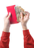 Räcka det hållande kinesiska röda kuvertet med pengar som isoleras på vit Arkivfoton