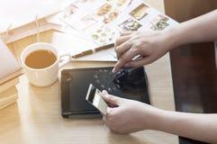 Räcka det hållande kortet och användaminnestavlan för on-line shoppinggods Arkivbild