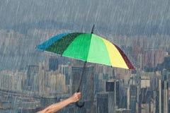 Räcka det hållande mångfärgade paraplyet med fallande regn på staden Royaltyfria Bilder