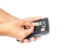 Räcka det hållande simkortet och sätt in i den isolerade smartphonen på vit Fotografering för Bildbyråer